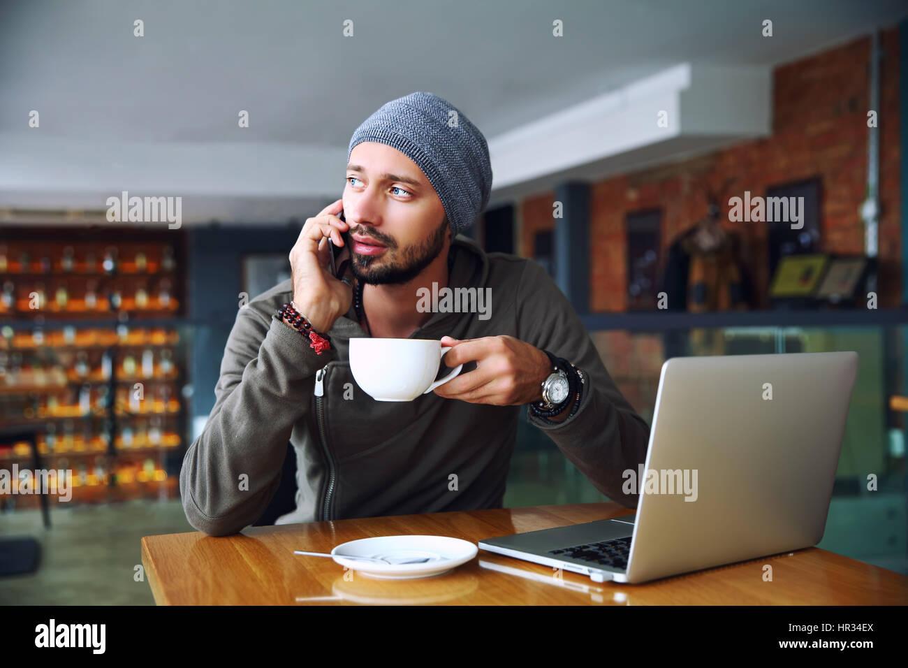Giovane bello hipster l uomo con la barba in seduta cafe parlando telefono mobile, tenendo tazza di caffè. Immagini Stock