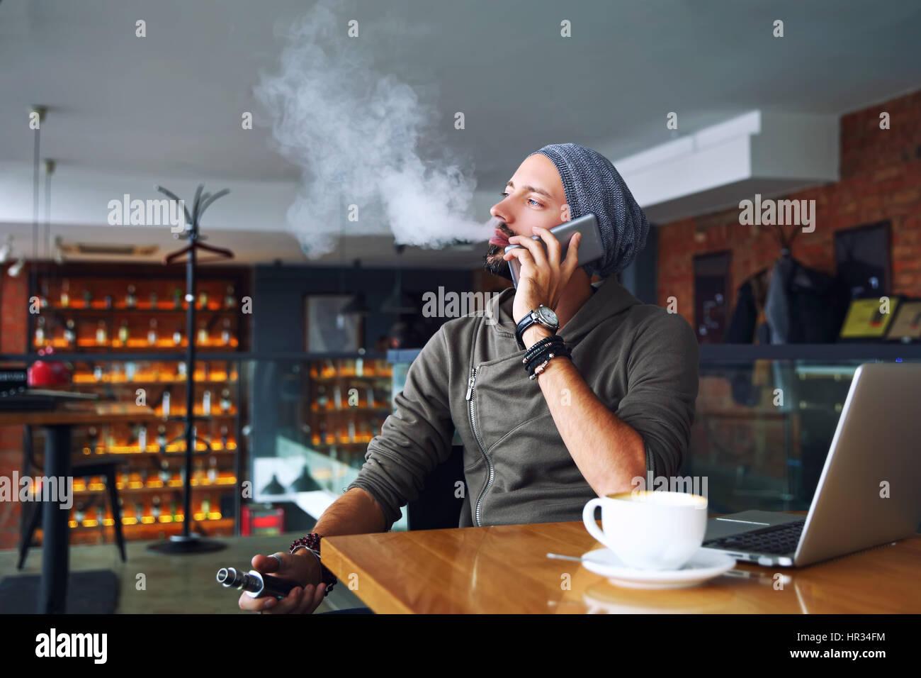 Giovane bello hipster l uomo con la barba seduto nella caffetteria con una tazza di caffè, vaping e rilascia Immagini Stock