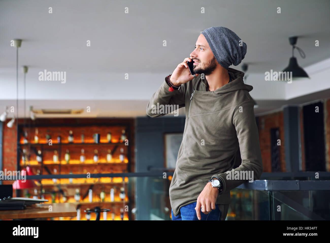 Giovane bello hipster uomo utilizza lo smartphone in cafe Immagini Stock