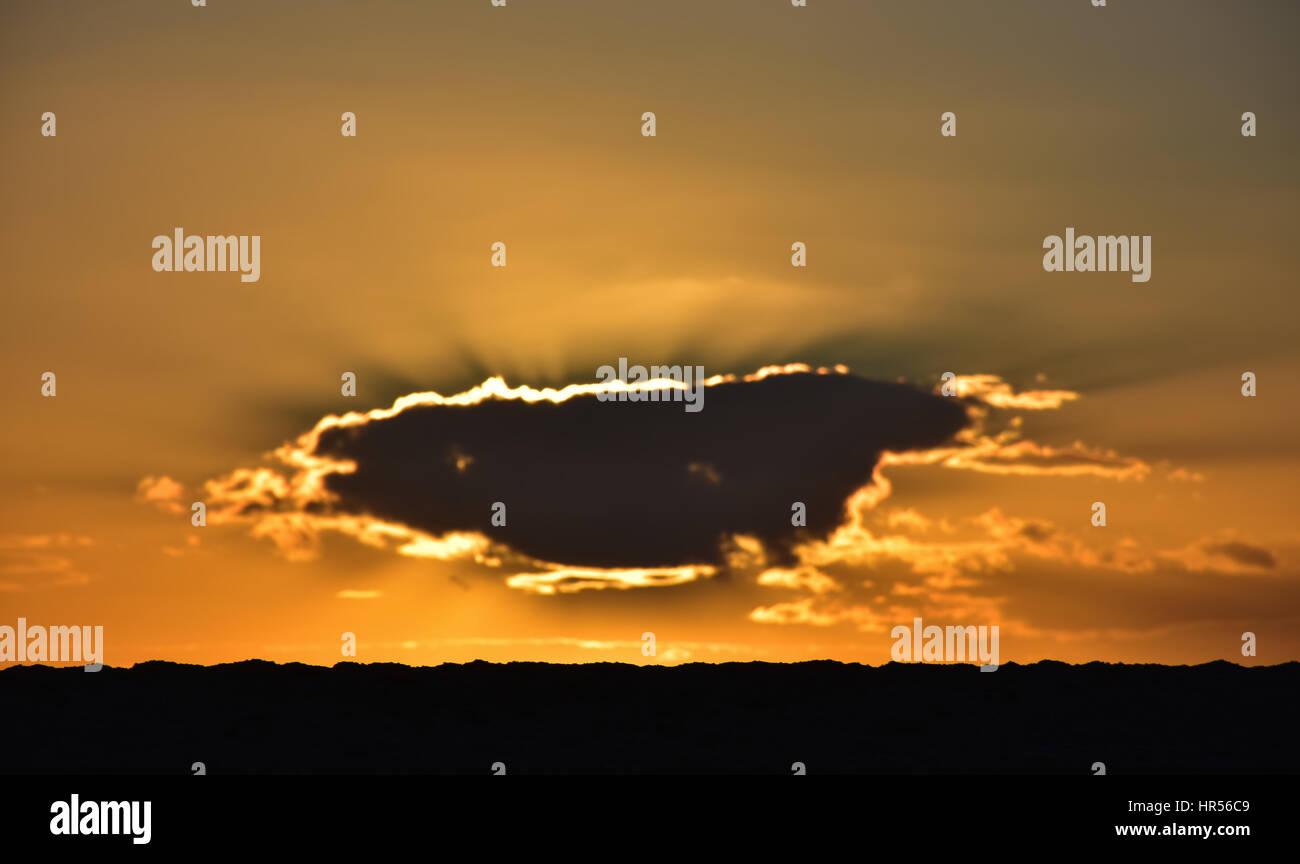 Sole che tramonta dietro il cloud e golden sky,Bridport,Dorset, Regno Unito. Foto Stock