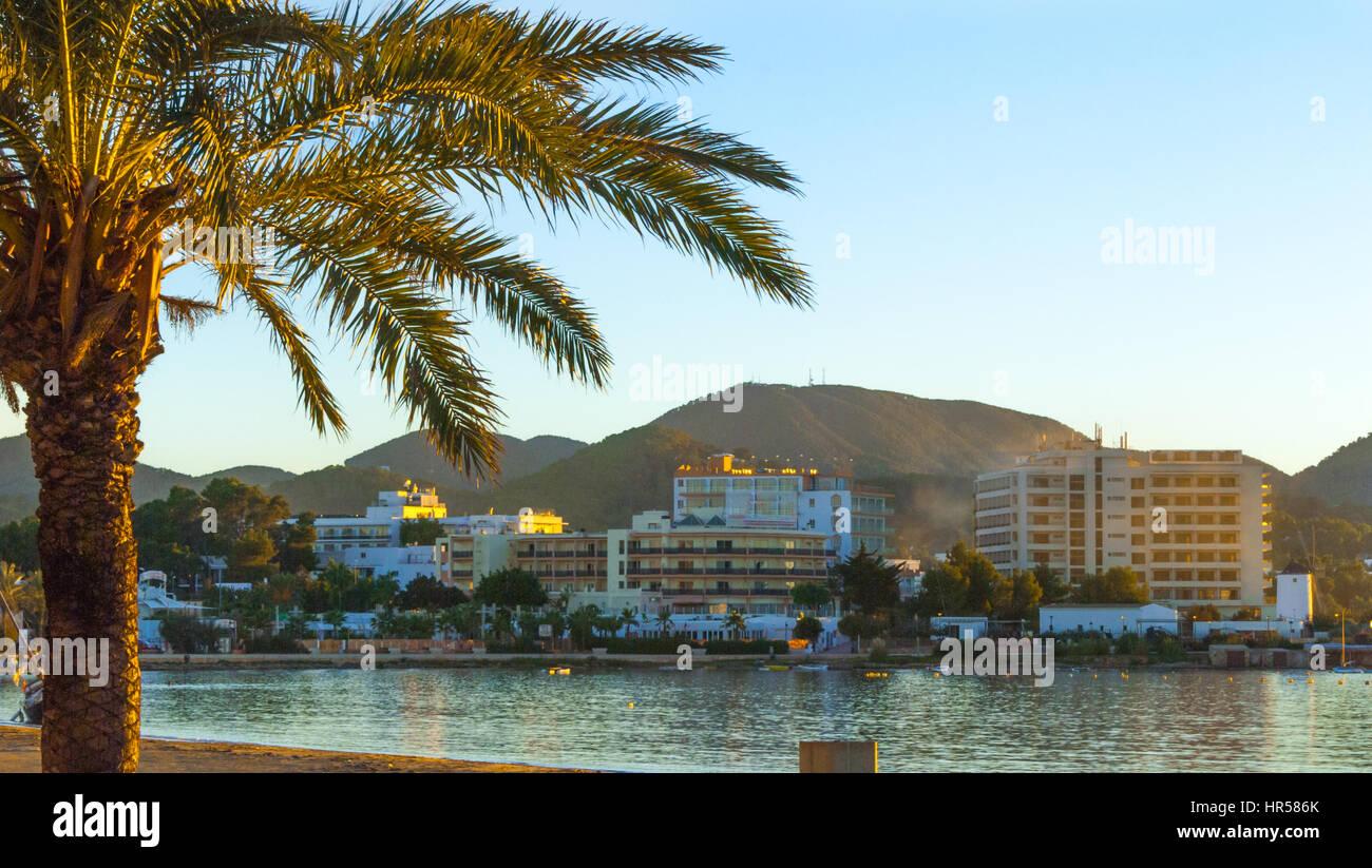 Nel tardo pomeriggio sole cade sulla baia. Sant Antoni de Portmany, Ibiza, Spagna. Alberghi lungo il litorale nella Immagini Stock