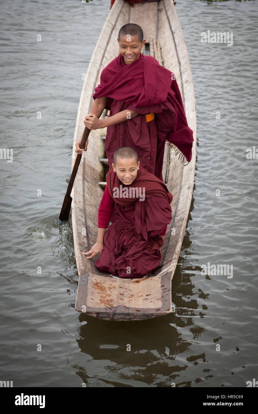 Il debuttante i monaci buddisti divertirsi su piccole imbarcazioni, a Maing Thauk (Myanmar). Giovani novizie sono Immagini Stock