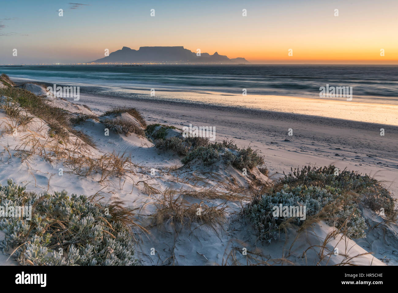 Vista della Table Mountain al tramonto dalla grande baia, Bloubergstrand, Cape Town, Sud Africa Immagini Stock