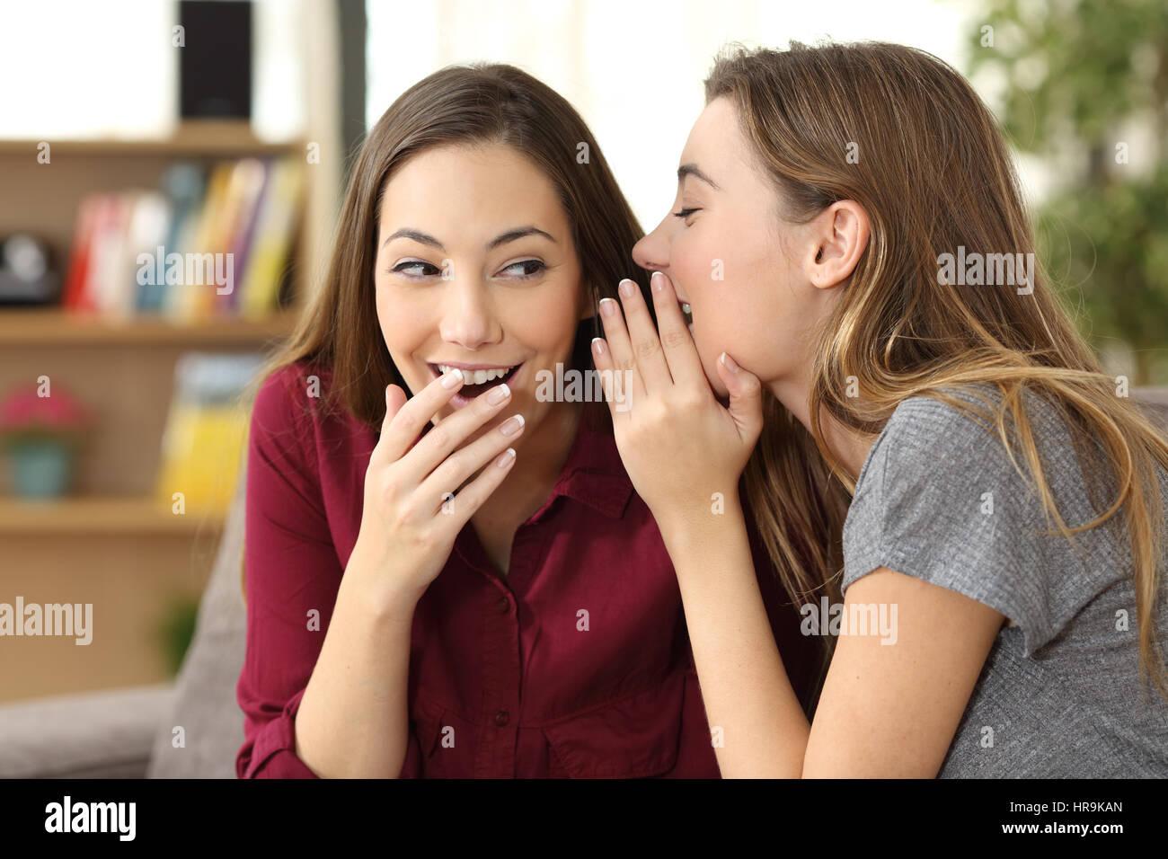 Ritratto di una ragazza di pettegolezzo raccontando un segreto in un orecchio per il suo amico seduto su un divano Immagini Stock
