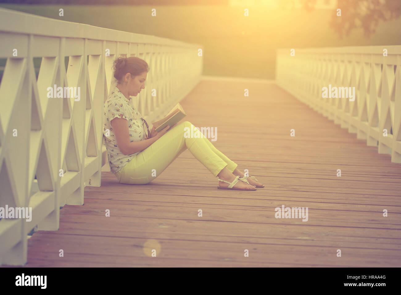 Apprendimento / lettura donna concetto nel tramonto Immagini Stock