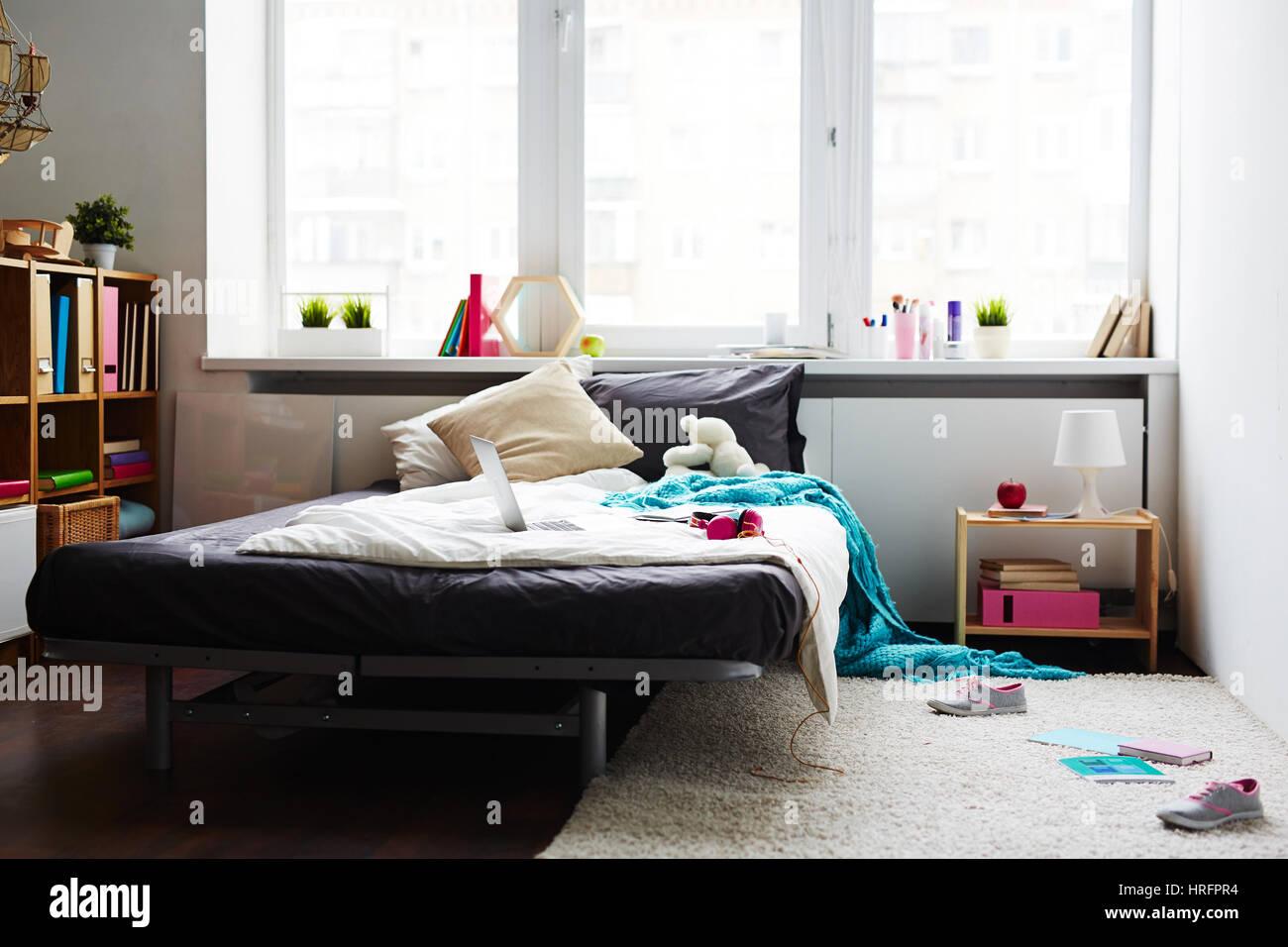 Moderna ragazza disordinato camera da letto con letto grande, laptop ...