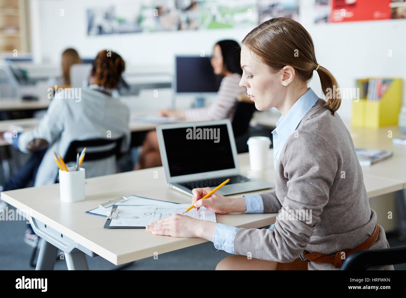 Occupato un piano aperto ufficio: piuttosto di mezza età interior designer seduto alla scrivania e fare schizzo Foto Stock