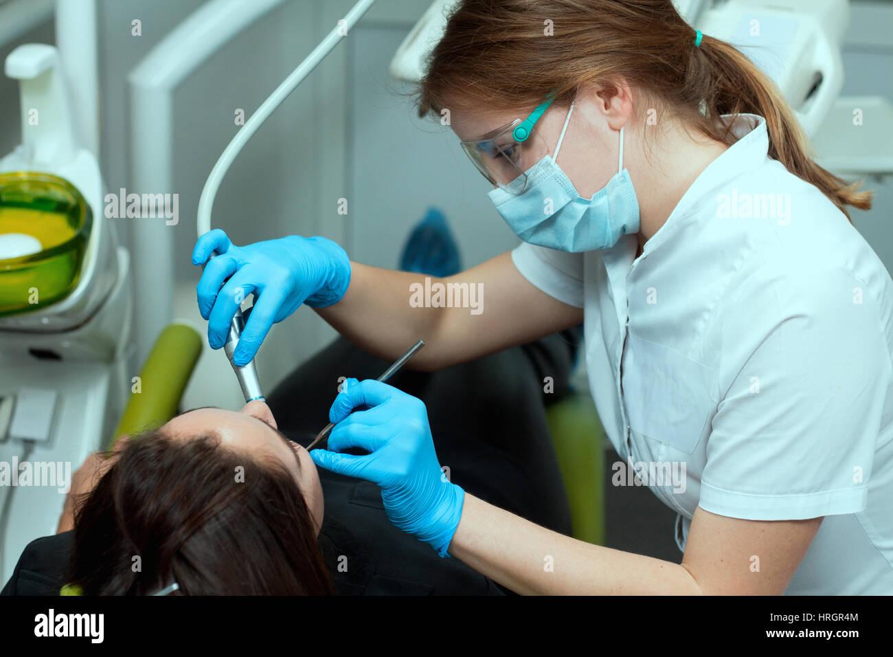 Paziente di sesso femminile presso il dentista trapanare il dente con una turbina e rendendo le otturazioni dentali Immagini Stock