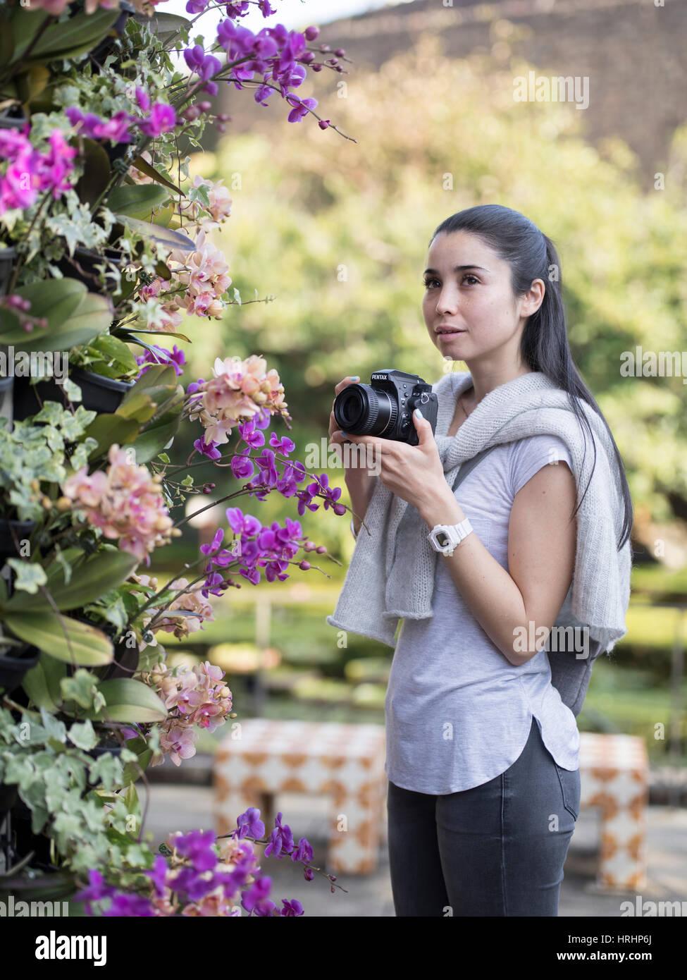 Giovane donna visualizzazione di orchidee tropicali al centro Dream, Giardino Botanico in Ocean Expo Park, Motobu, Immagini Stock