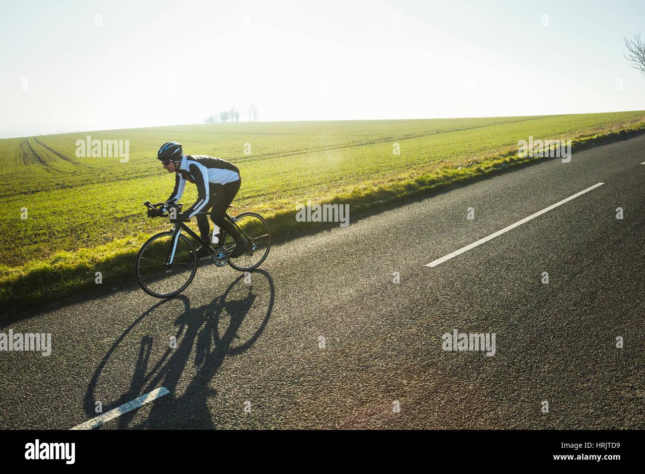Un ciclista a cavallo, lungo una strada di campagna su una chiara soleggiata giornata invernale. Ombra sulla superficie della strada. Foto Stock
