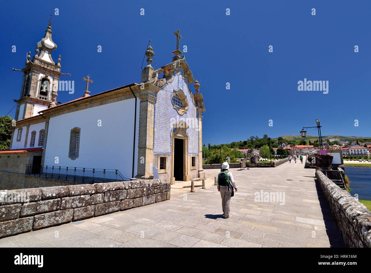 Portogallo: Donna con zaino camminando lungo il ponte romano e la cappella medievale di San Giacomo modo fermata Immagini Stock