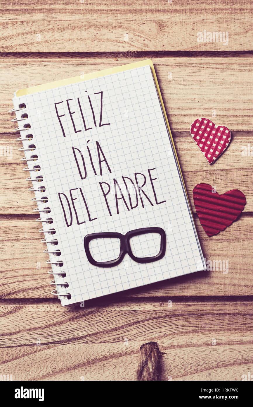 Il testo feliz dia del padre, padri felice giorno in spagnolo scritto nella pagina di un notebook, un paio di occhiali Immagini Stock