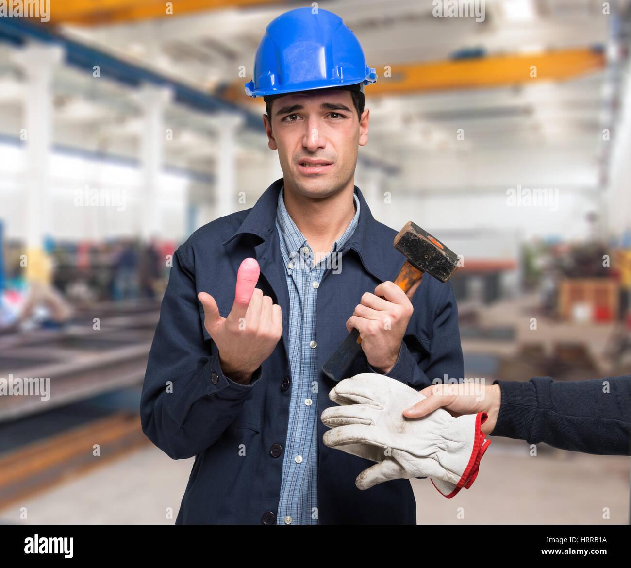 Lavoratore colpito da un colpo di martello sul suo dito Immagini Stock