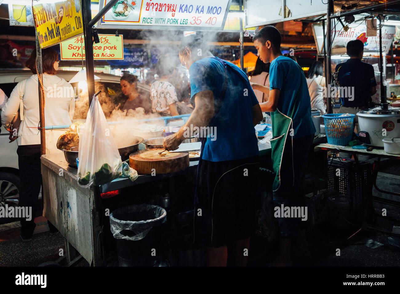 Chiang Mai, Thailandia - Agosto 27, 2016: Padre e sun la cottura di alimenti al sabato notte di mercato il 27 agosto Immagini Stock