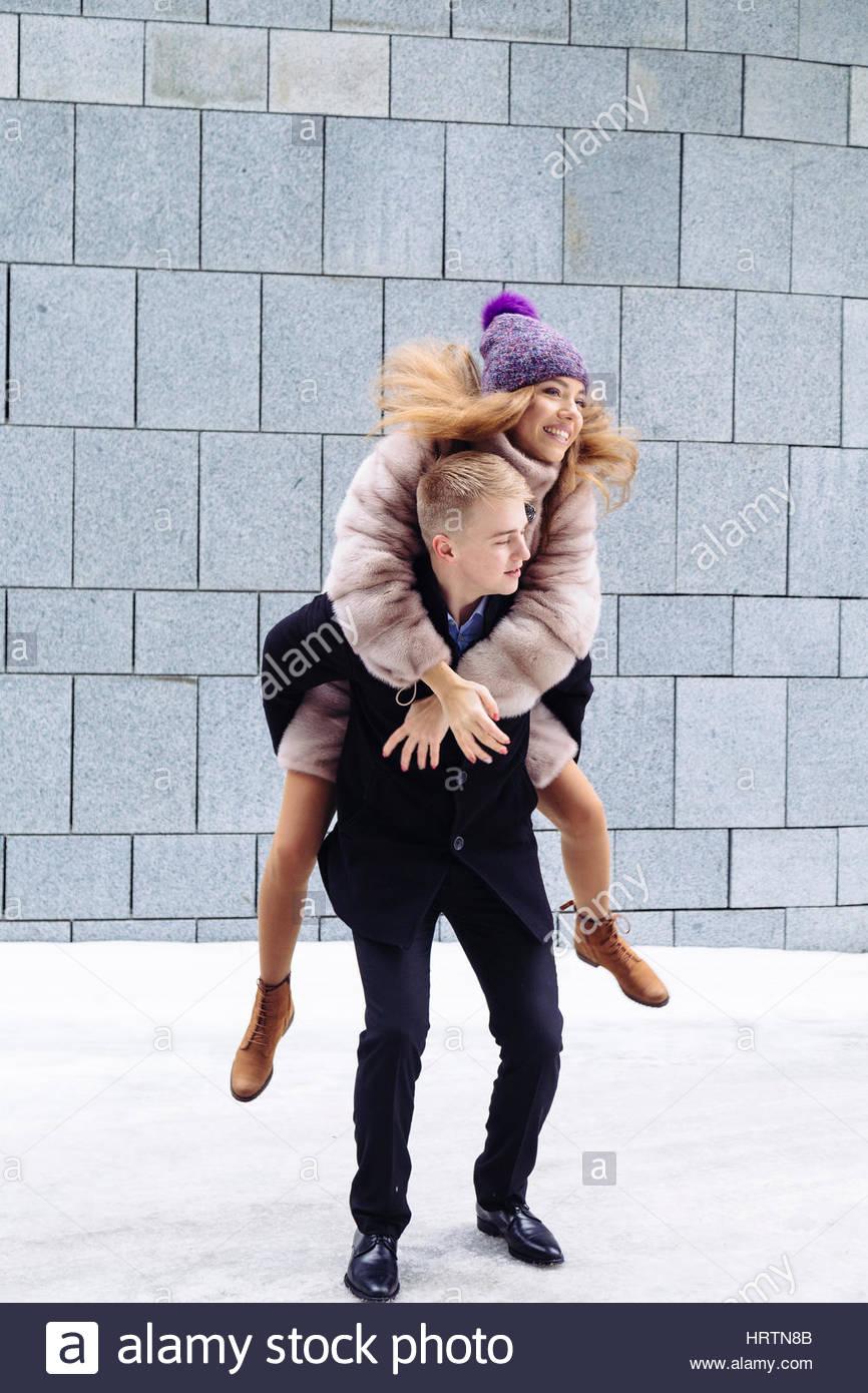 Ritratto di un uomo bello piggybacking la sua fidanzata in vacanza. concetto di relazione. Immagini Stock