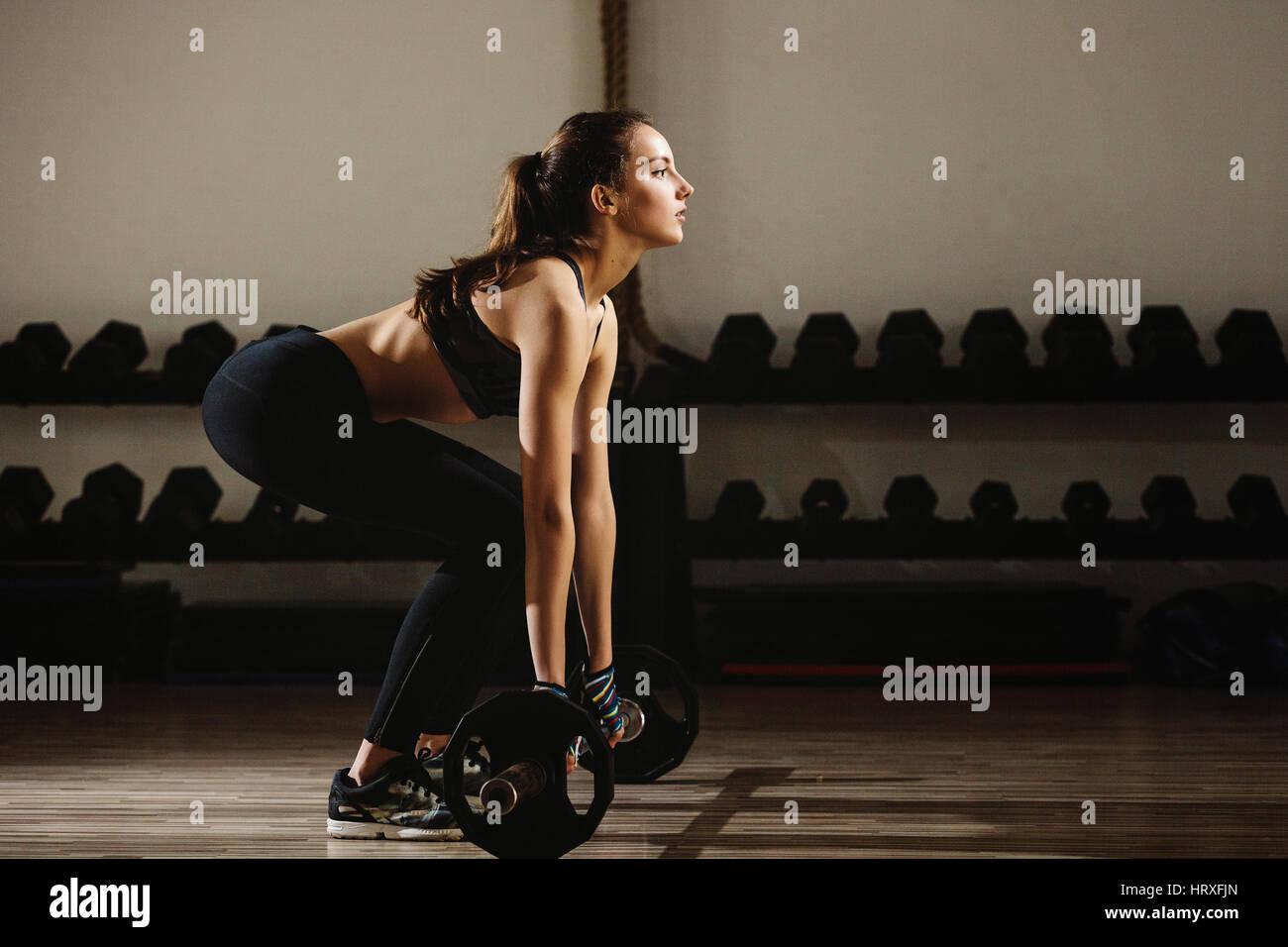 Donna fitness pesi deadlift. Modello di fitness girl il sollevamento pesi in palestra. Immagini Stock