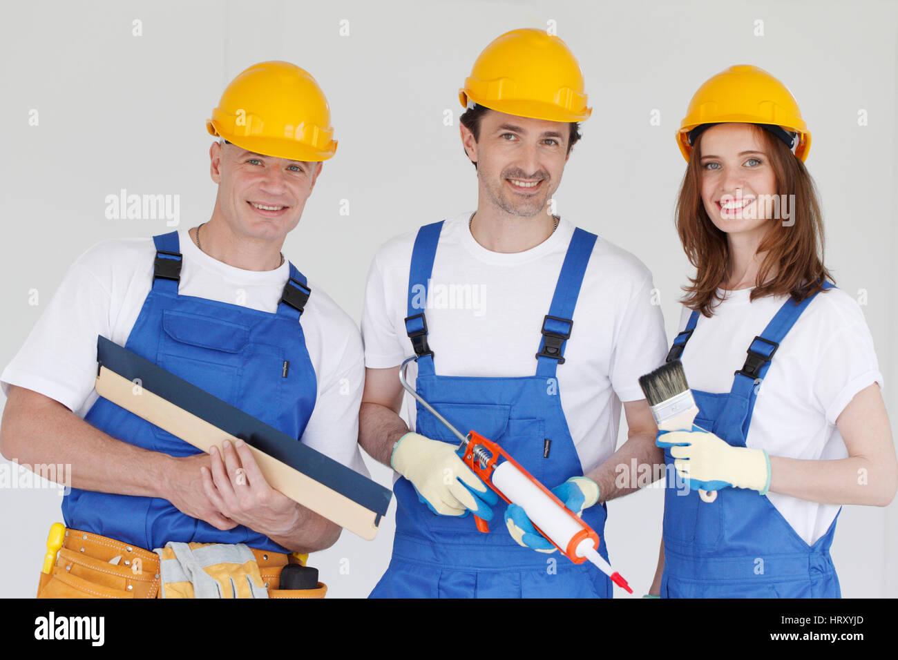 Team di allegro lavoratori in uniforme e hardhats con strumenti Immagini Stock