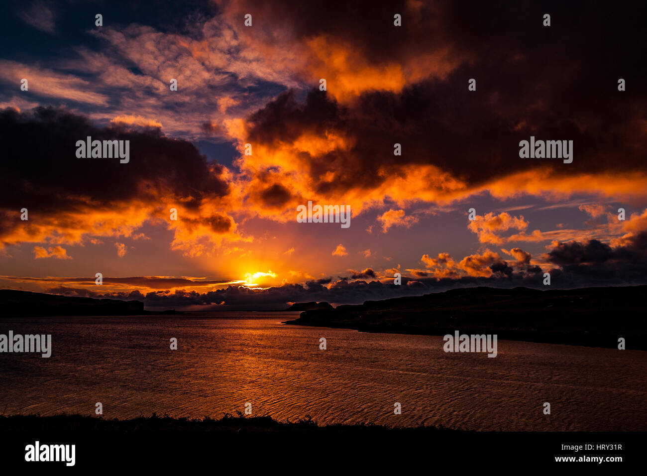 Tramonto con luce crepuscolare sul Loch Beag, Isola di Skye, guardando fuori al punto Ullinish, Bracdale punto punto Ardtreck e Isola Oronsay Foto Stock