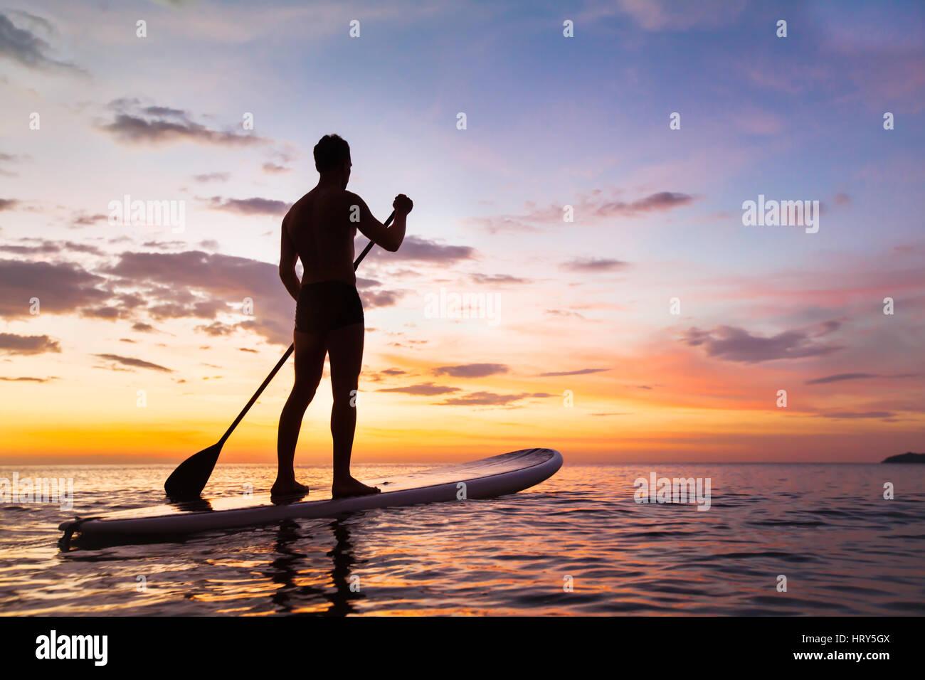 Paddleboard sulla spiaggia al tramonto, paddle in piedi in Thailandia Immagini Stock