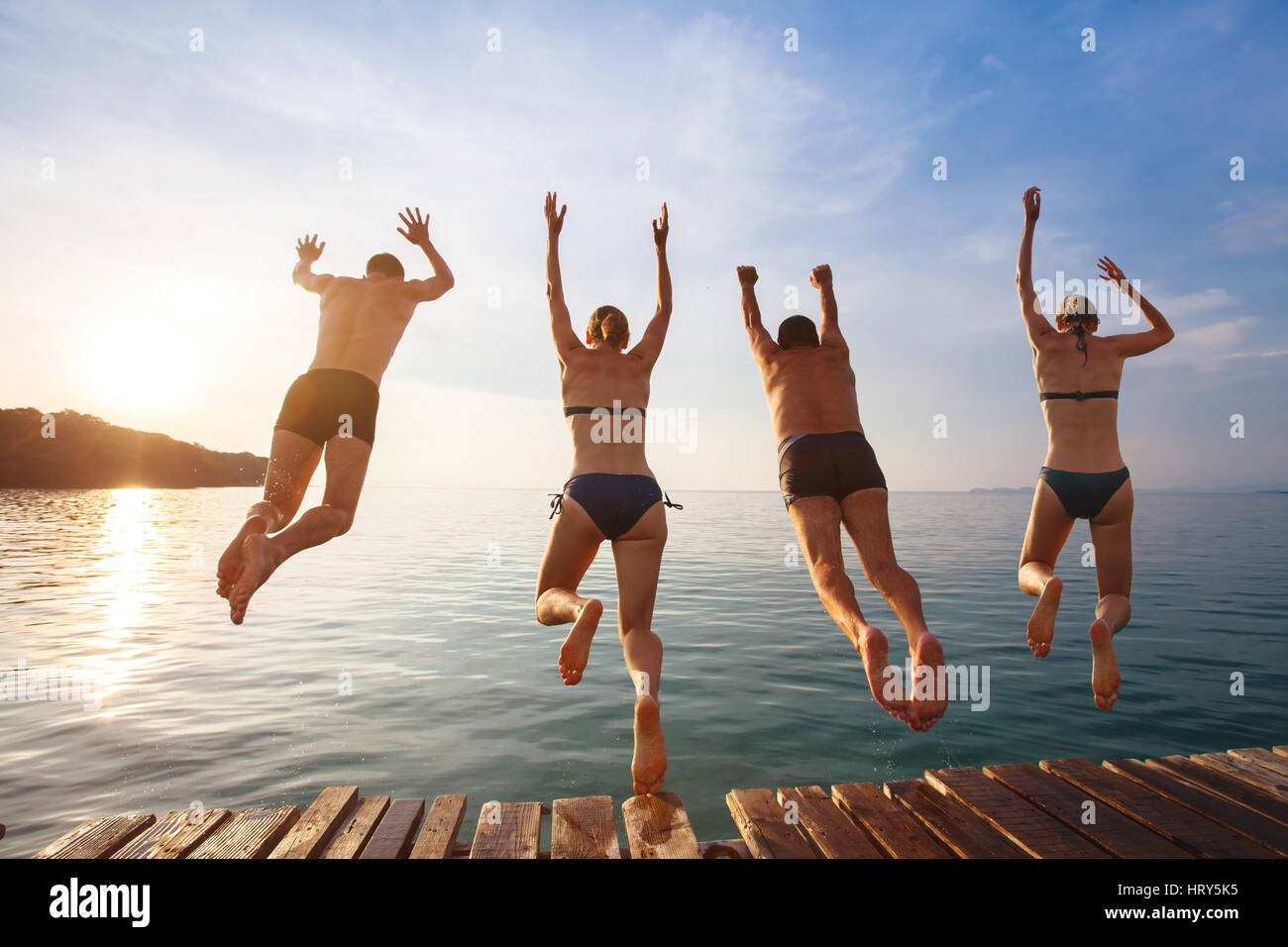 Gruppo di amici jumping al mare dal molo, felici vacanze in spiaggia Immagini Stock