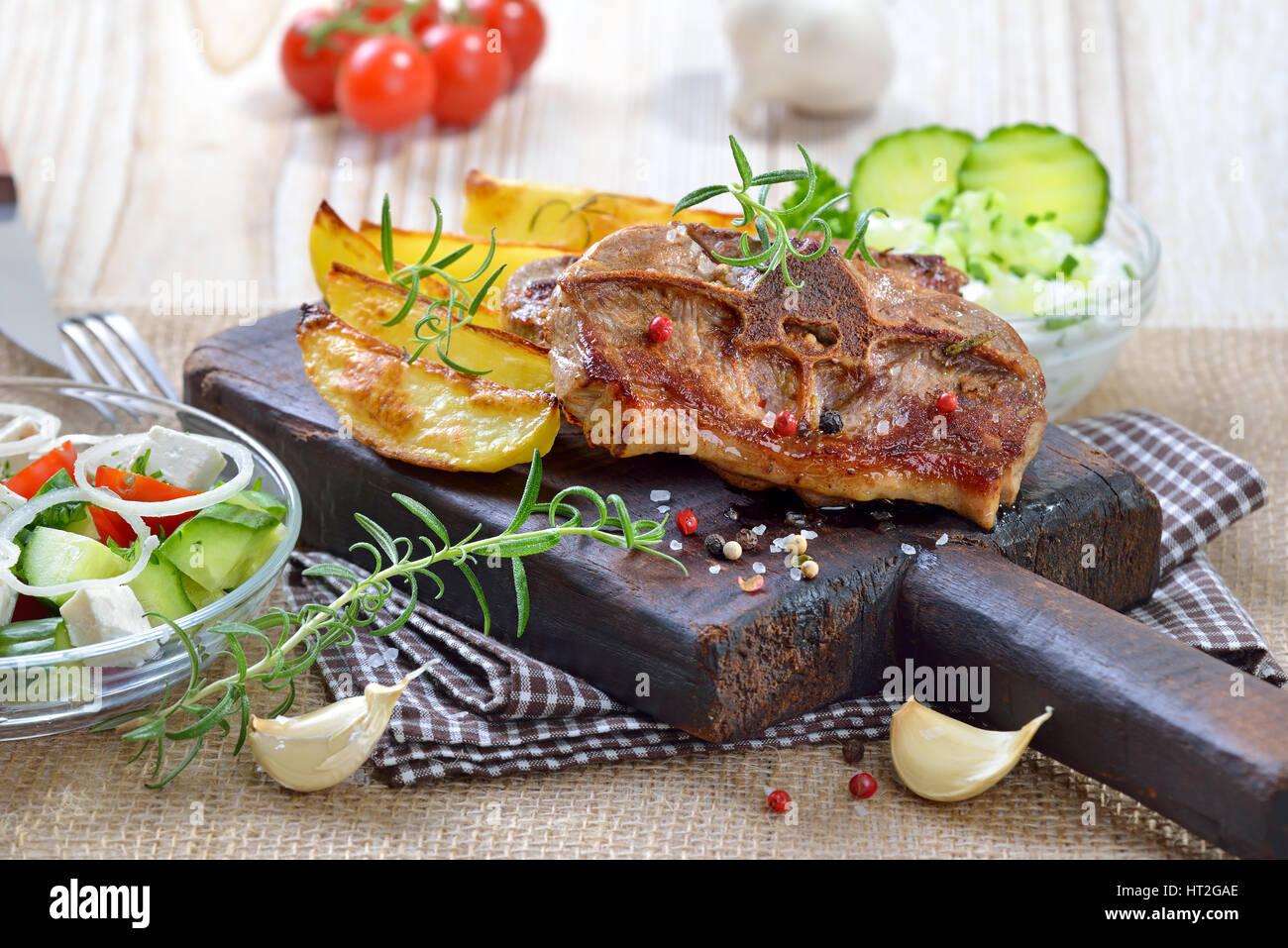 Pasto greco: fritto costolette di agnello con patate al forno cunei, agricoltori e insalata tzatziki Immagini Stock