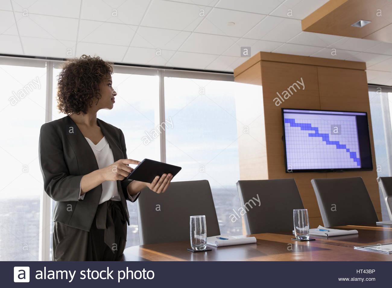 Imprenditrice con tavoletta digitale preparazione presentazione audio visiva in sala conferenze Immagini Stock