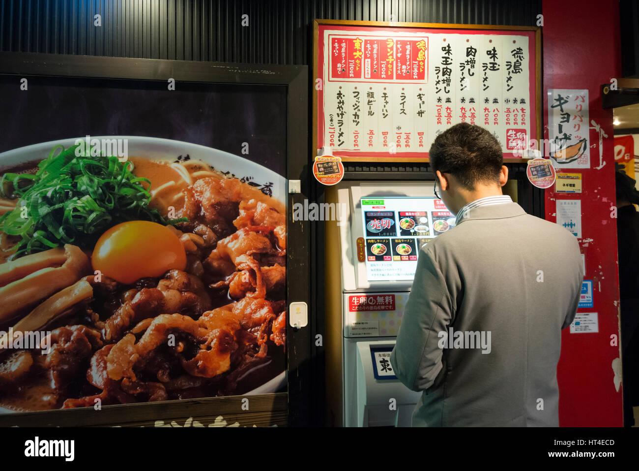 Un uomo di pagare per il cibo in un distributore automatico in anticipo prima di entrare nel ristorante, Kyoto, Immagini Stock
