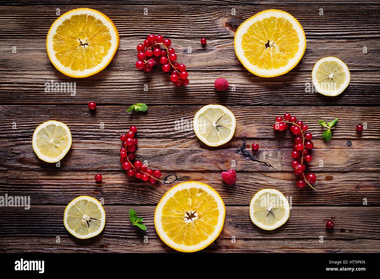 Limone e anelli di arancione, rosso Ribes, lamponi e foglie di menta su sfondo di legno. Tabella vista dall'alto. Immagini Stock