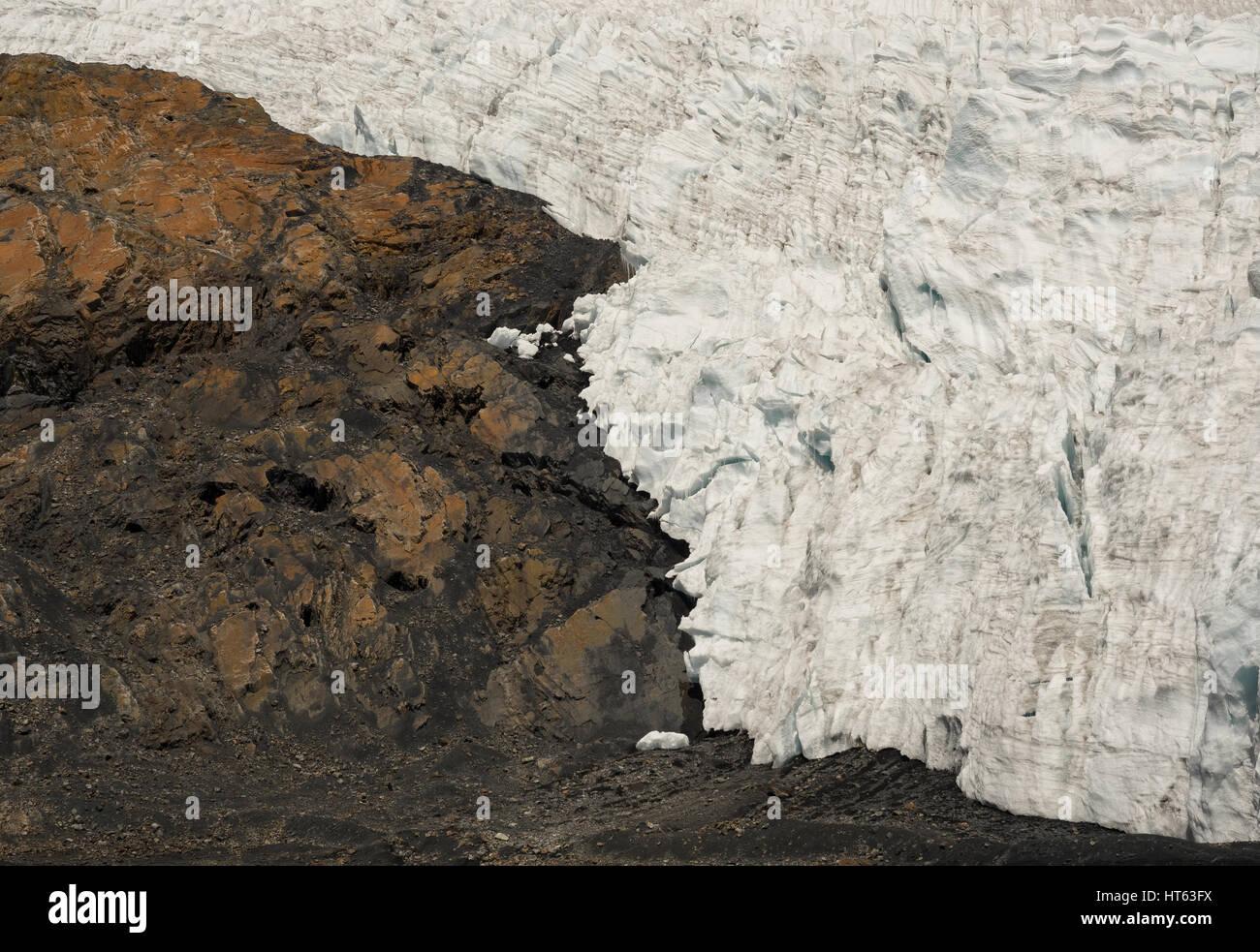 Il confine tra il ghiaccio del ghiacciaio di restringimento e la roccia di una montagna che simboleggiano il cambiamento Immagini Stock