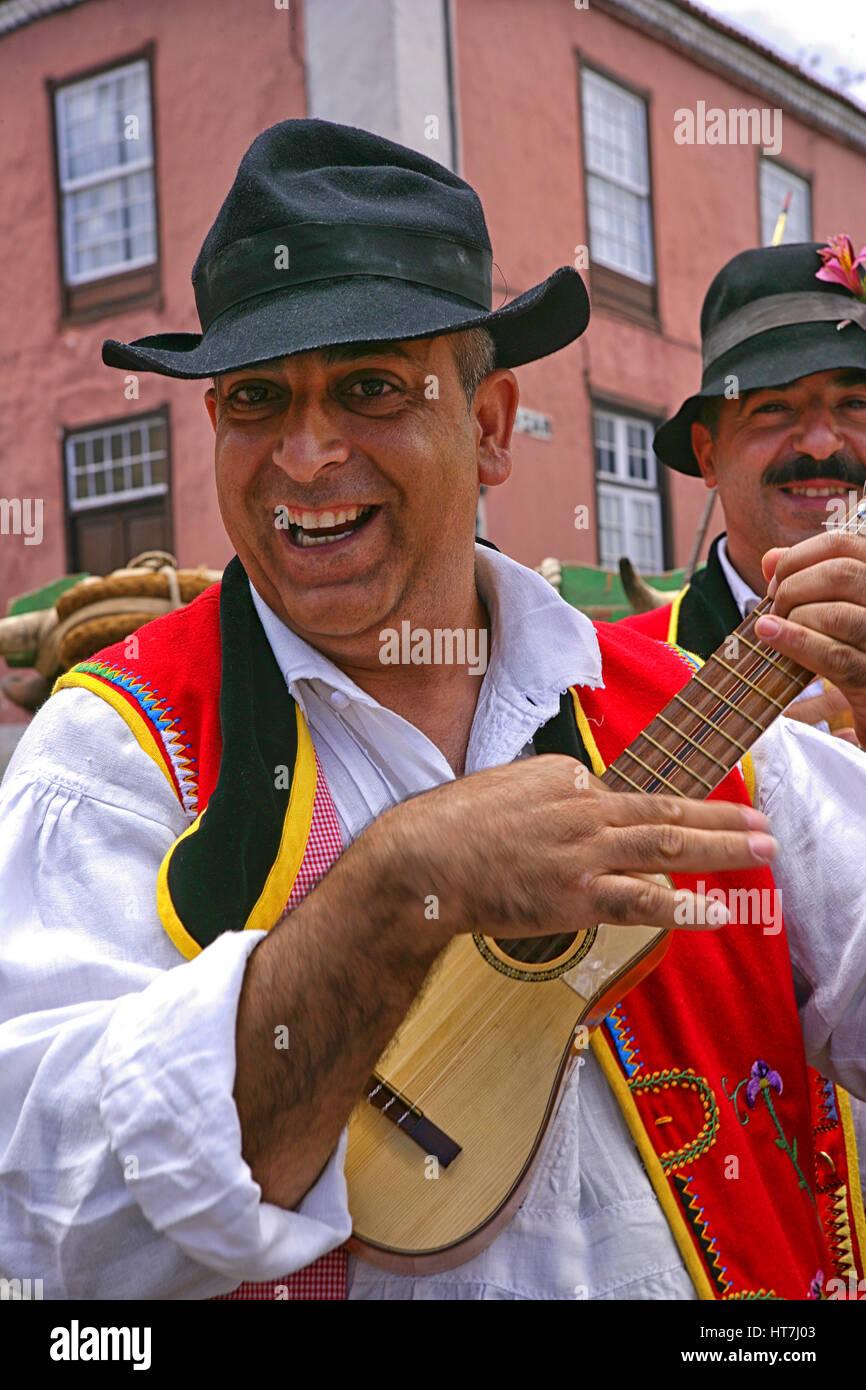 Ritratto di un uomo sorridente in un abito tradizionale giocando Ukelele Immagini Stock