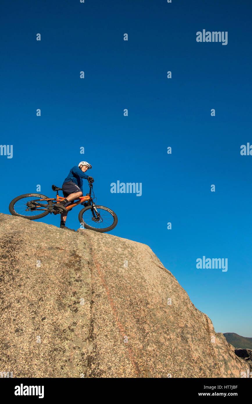 Basso angolo vista di Alex Leich con Mountain Bike sul nudo di lastre di granito in North Conway, New Hampshire Immagini Stock