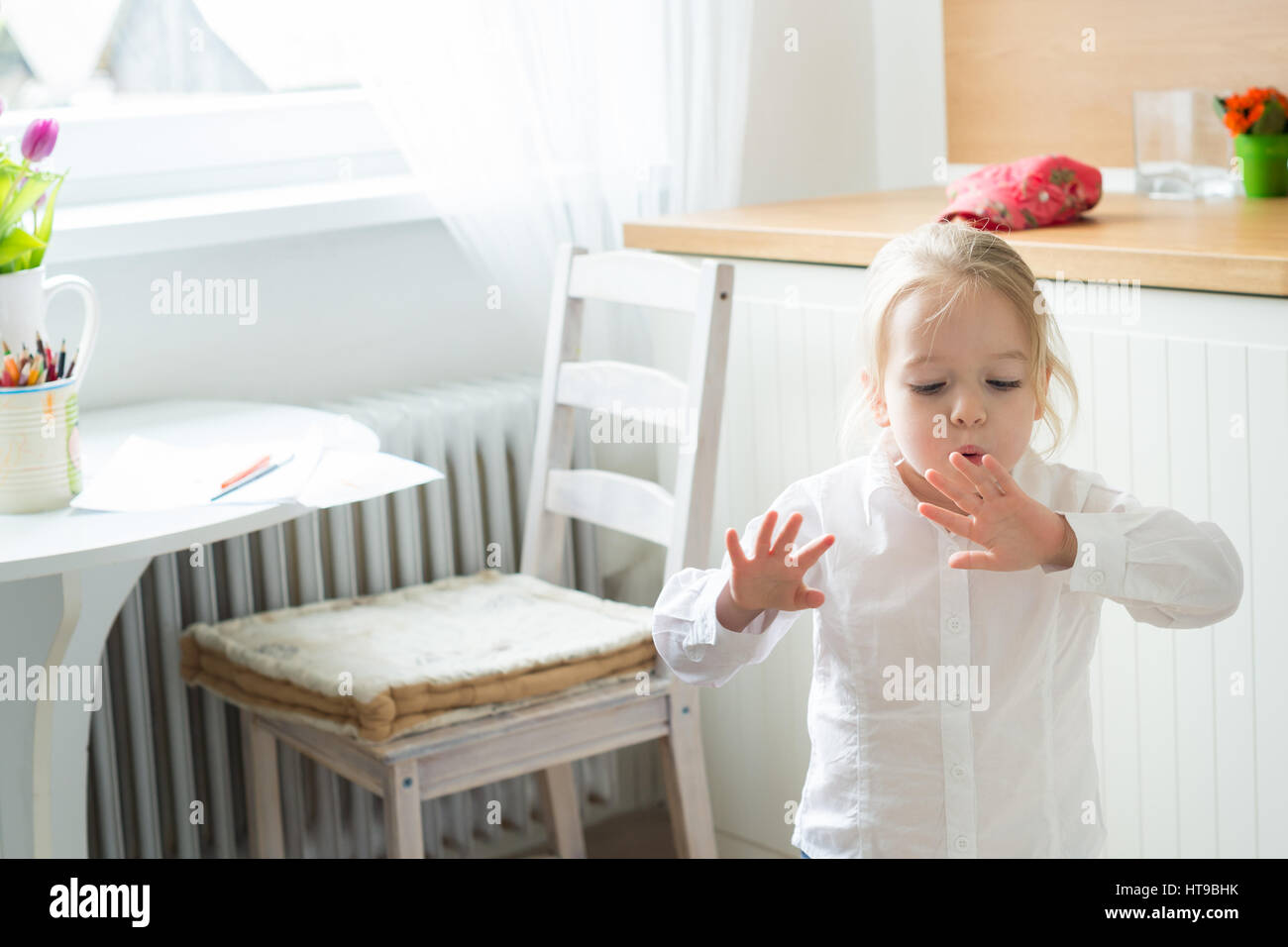 Bambina cercando di asciugare la sua dipinta di fresco unghie Immagini Stock