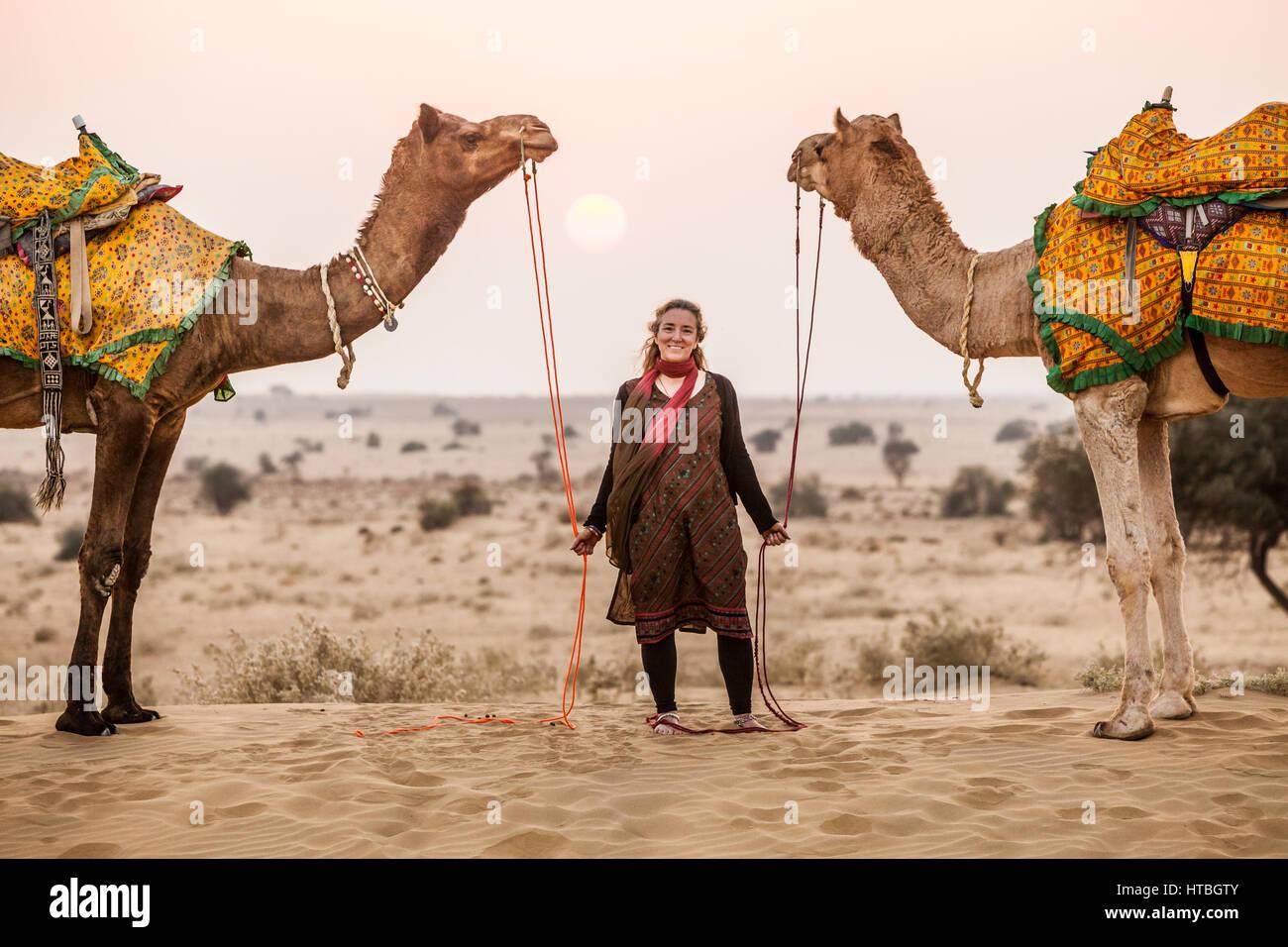 Una donna che posano per una foto con due cammelli nel deserto di Thar al tramonto, Rajasthan, India. Immagini Stock