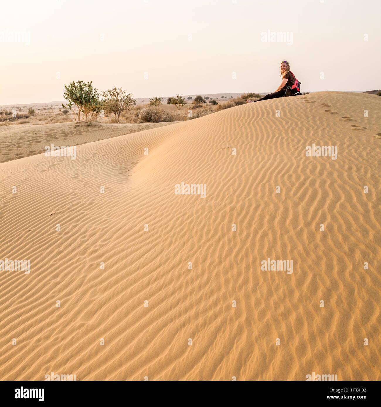 Una donna seduta su una duna di sabbia nel deserto del Thar al tramonto, Rajasthan, India. Immagini Stock