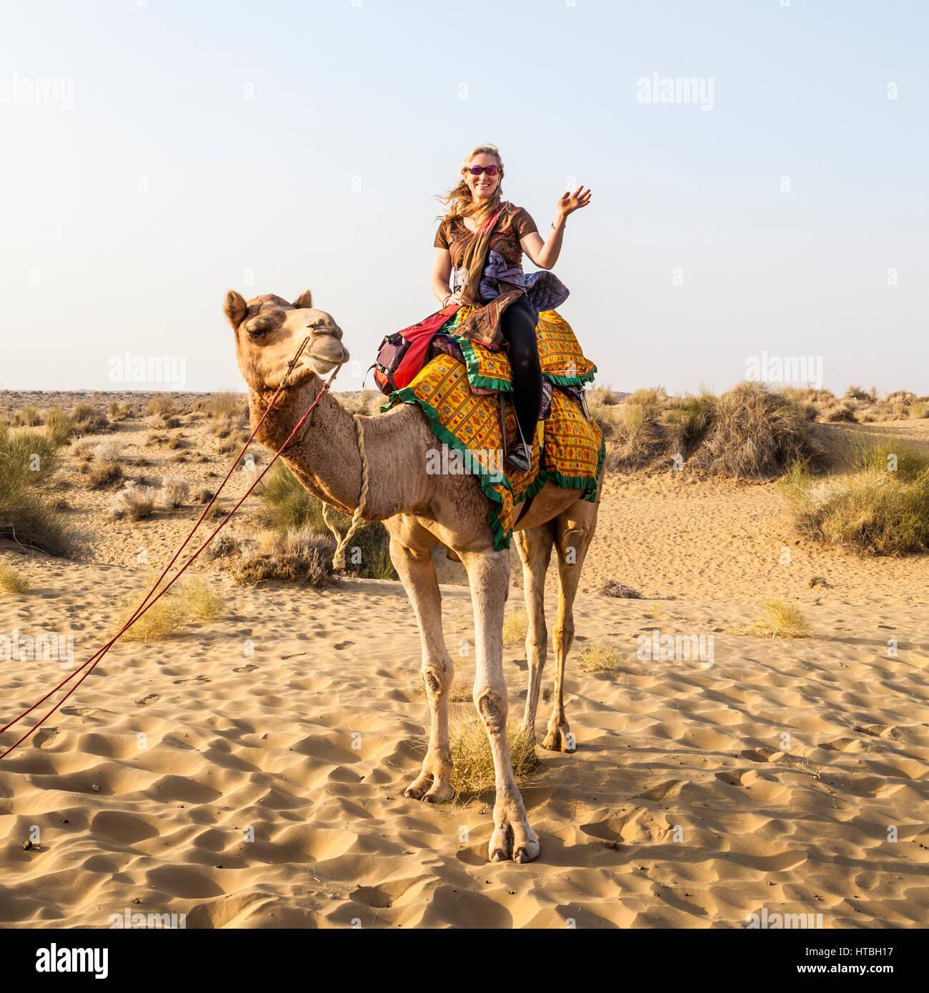 Una donna gesticolando e sorridente sulla cima di un cammello ella è equitazione, il deserto di Thar, Rajasthan, Immagini Stock