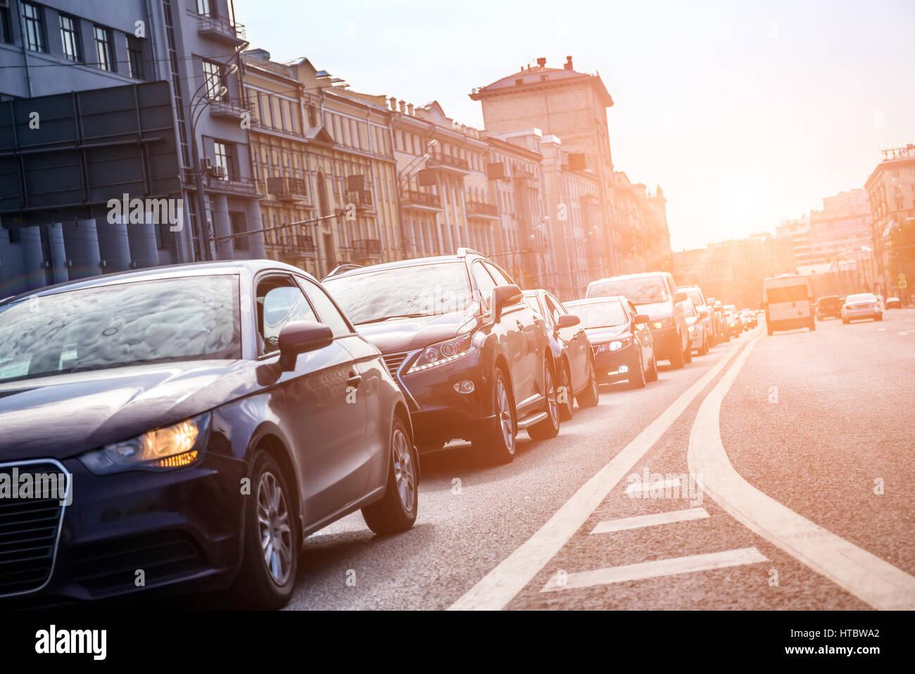 Vista dal basso verso la corsia con le automobili nel traffico con la calda luce del sole Immagini Stock