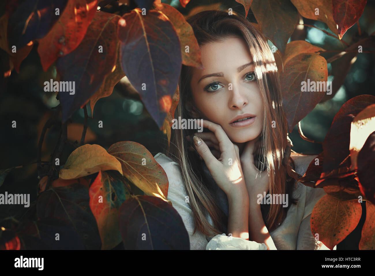 Bella giovane donna in posa tra colorate Foglie di autunno Foto Stock