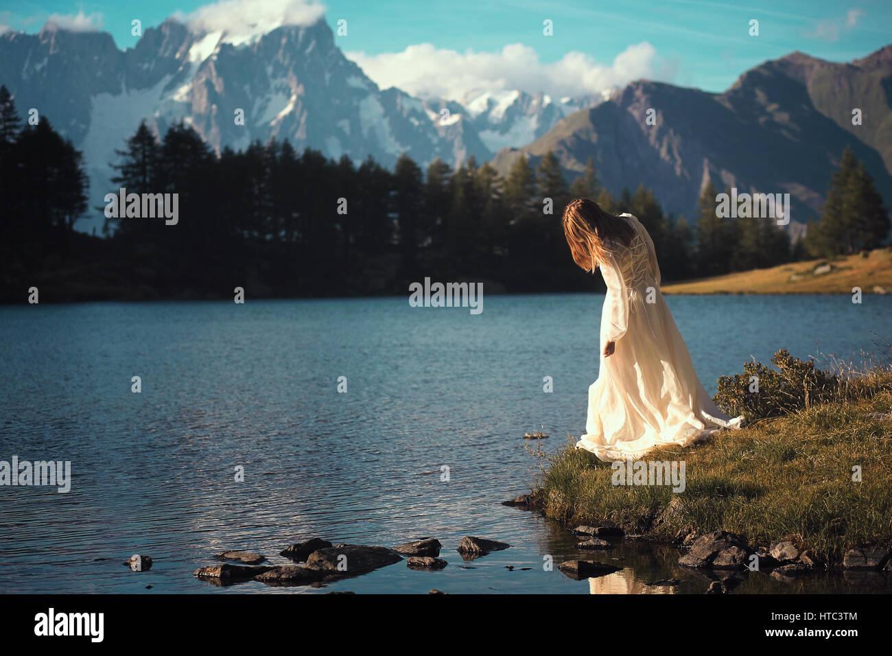Donna in posa di lago di montagna al tramonto. Romantico e sognante Immagini Stock
