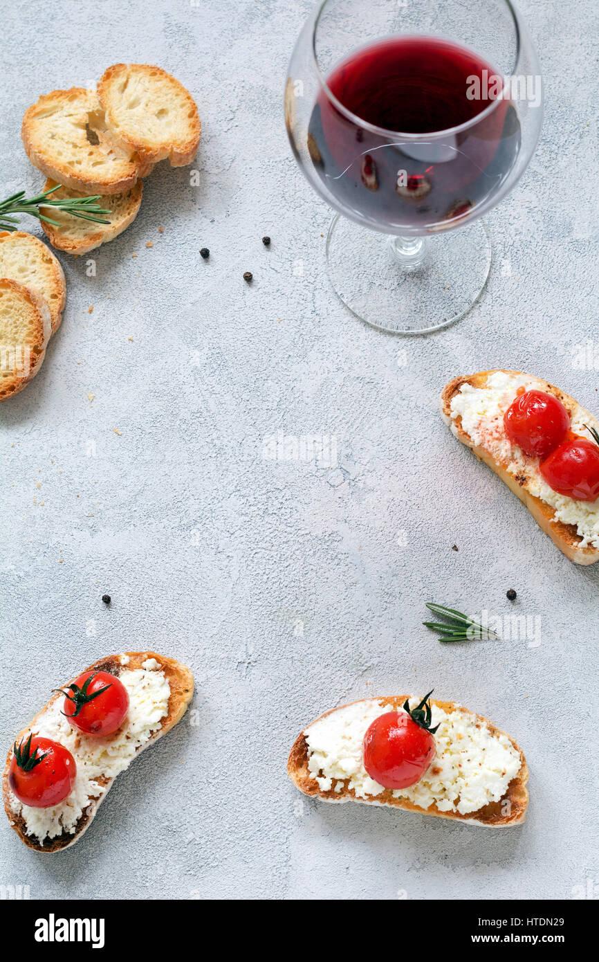Antipasto Italiano Bruschetta con formaggio fresco e pomodorini e bicchiere di vino rosso. Copia spazio per il testo. Immagini Stock
