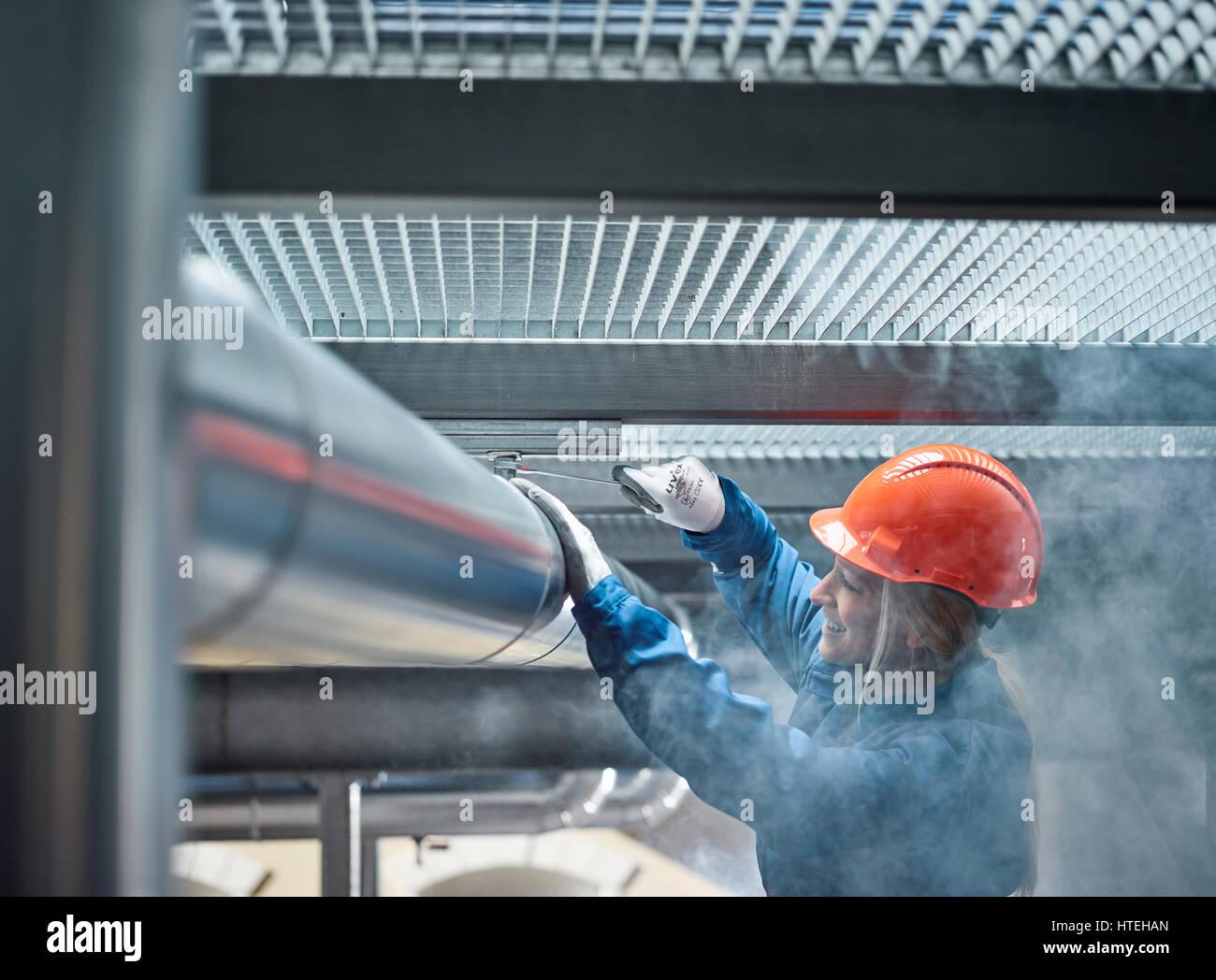 Tecnico meccanico con un casco arancione il montaggio di una linea di refrigerazione staffa, Austria Immagini Stock