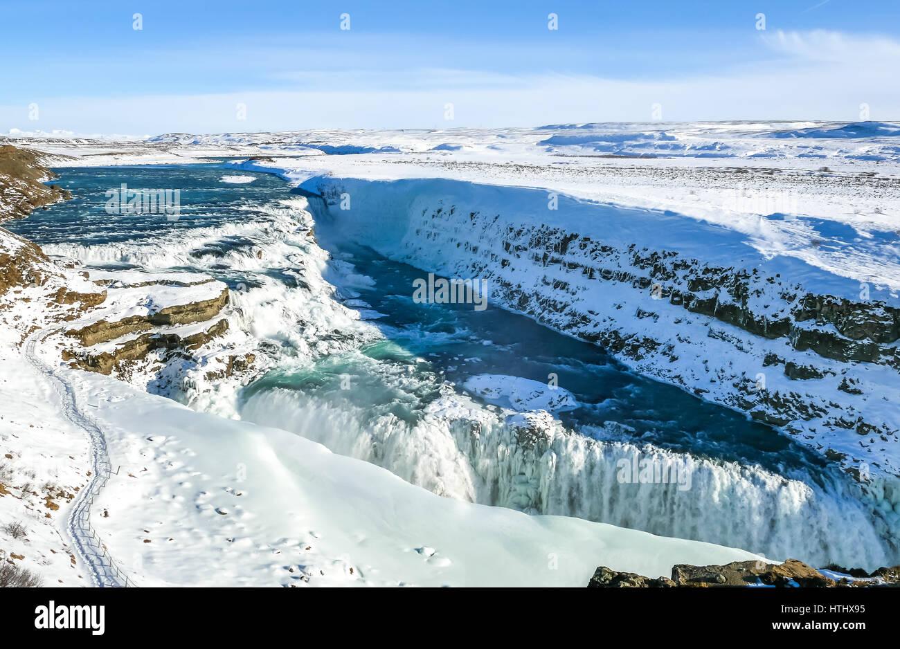 Guardando oltre il bordo della scogliera a due tier cascate gelate, Gullfoss, Golden Circle, Islanda Foto Stock