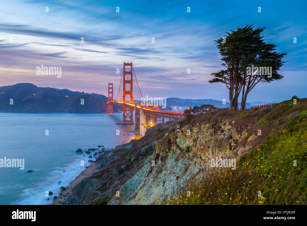 Classic vista panoramica del famoso Golden Gate Bridge visto da scenic Baker Beach in splendida post tramonto crepuscolo Immagini Stock