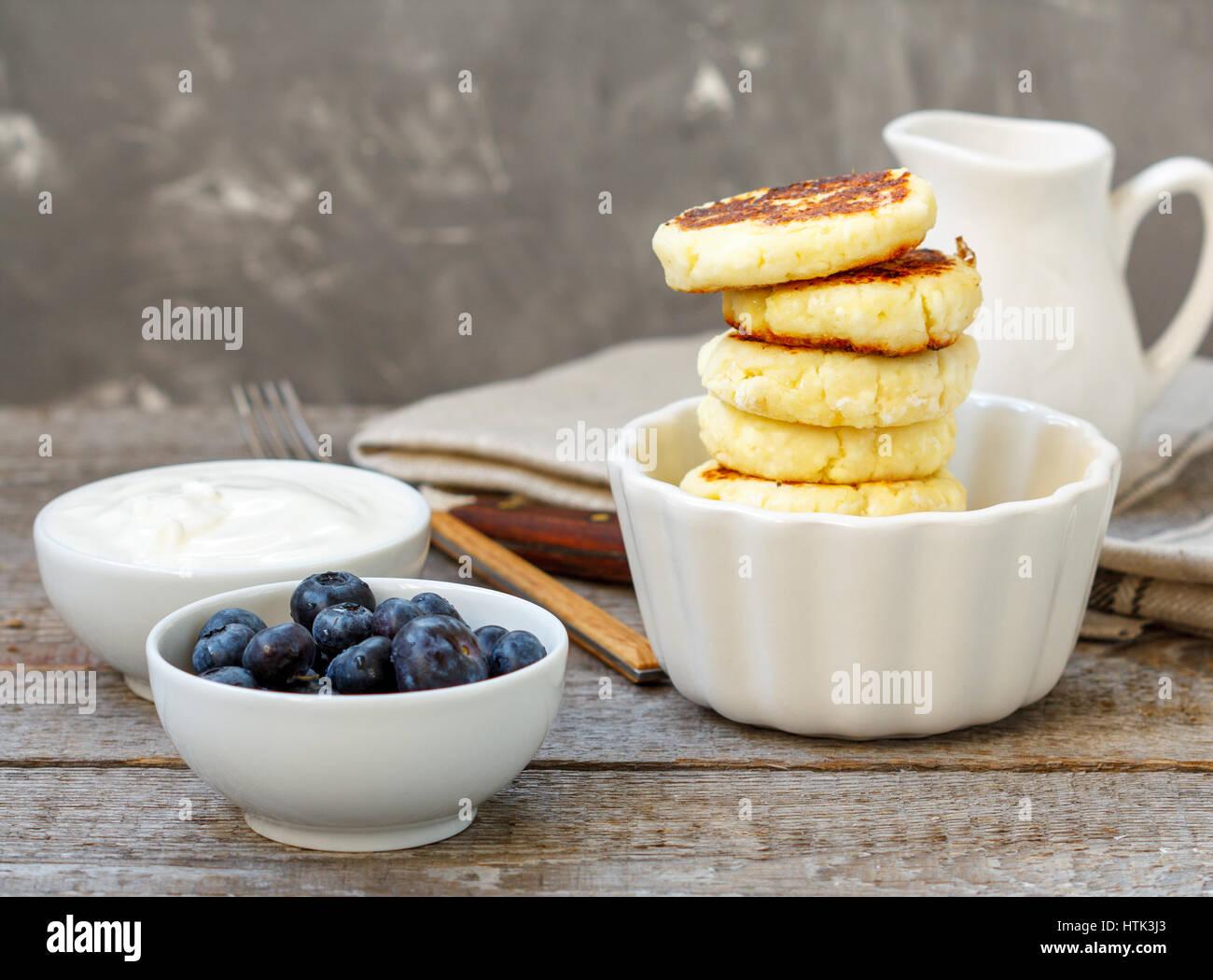 Cottage cheese pancakes per colazione con mirtilli e panna acida. Immagini Stock