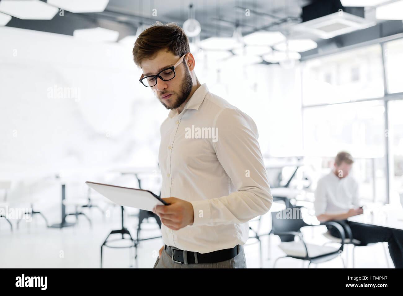 Fiducioso imprenditore indossando maglietta e occhiali che usano tablet Immagini Stock