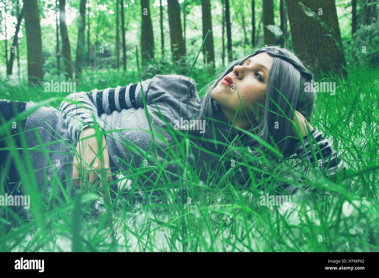 Giovane donna con i capelli grigi in una foresta Immagini Stock