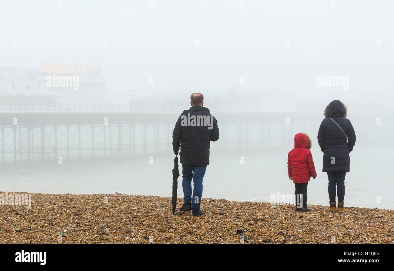 Famiglia su di una spiaggia in riva al mare su un nebbioso giorno in Brighton, East Sussex, Inghilterra, Regno Unito. Immagini Stock