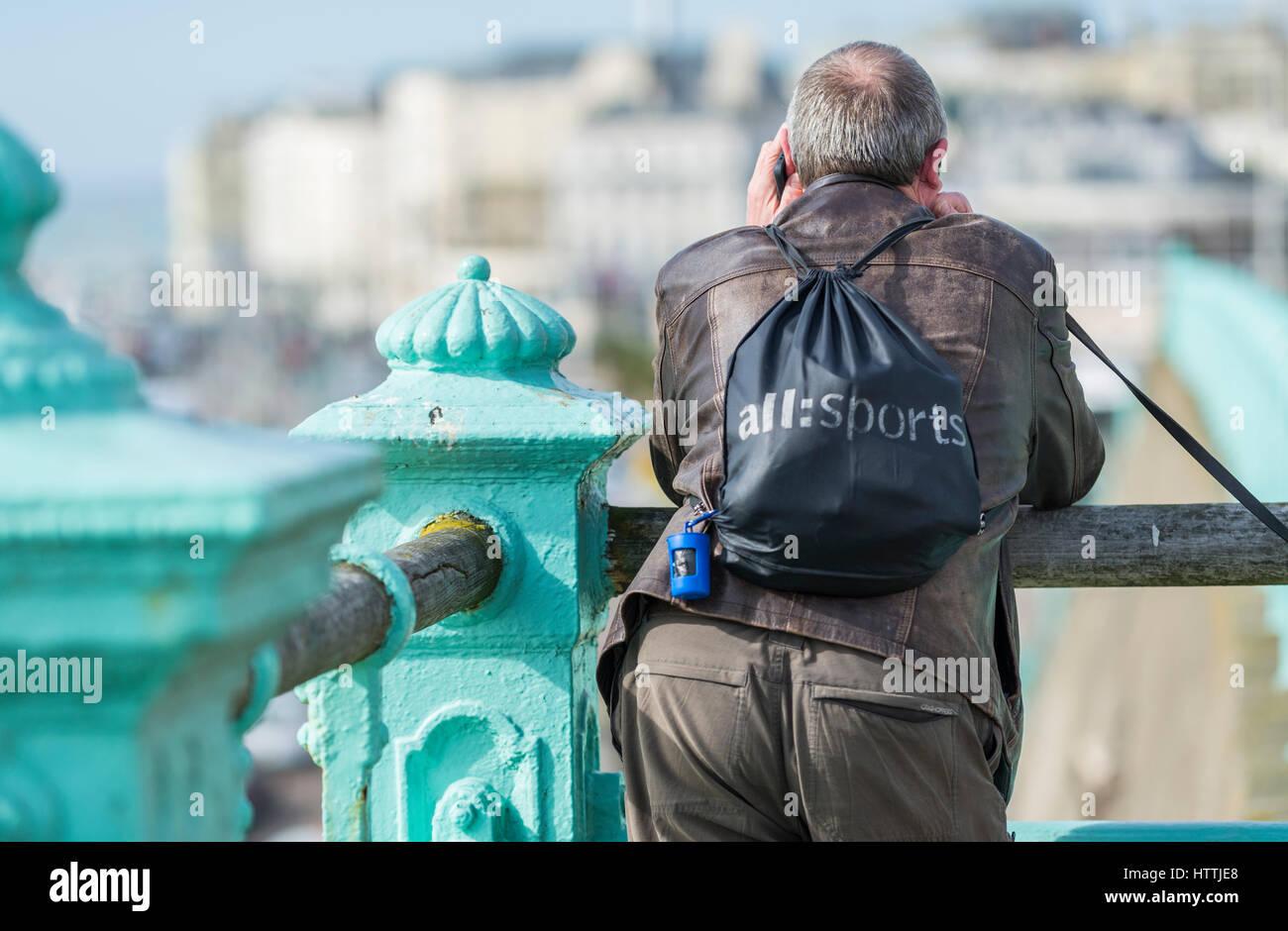Uomo in piedi su ringhiere mentre si parla sul suo telefono cellulare. Immagini Stock