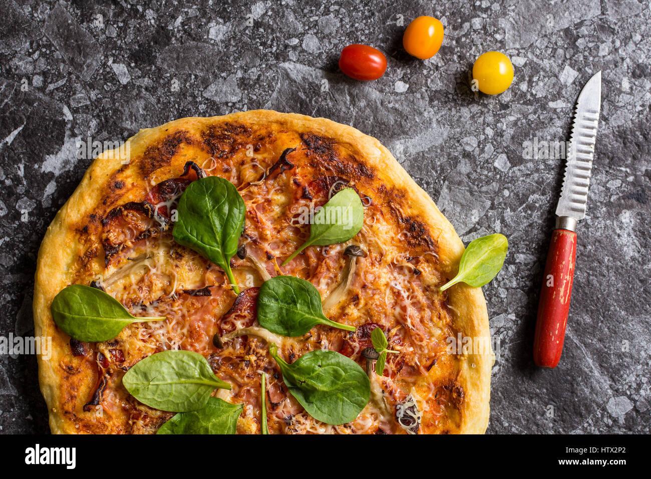 La pizza fatta in casa con formaggio, prosciutto, salame, baby spinaci e funghi shimeji. Sfornato fresco il cibo Immagini Stock