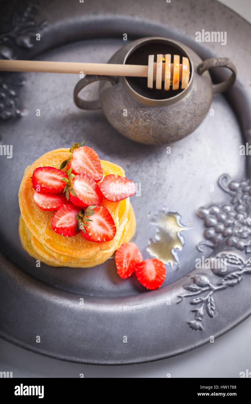 Pila di frittelle dolci con fragola e miele. Immagini Stock