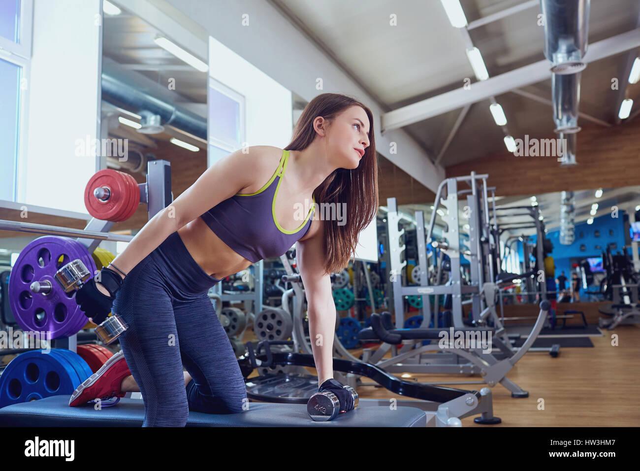 Giovane ragazza sportiva con manubri in mani facendo esercizi in spo Immagini Stock